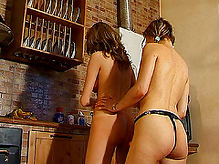 Horny lesbian has her pink slit jammed with a strap on dildo in the kitchen